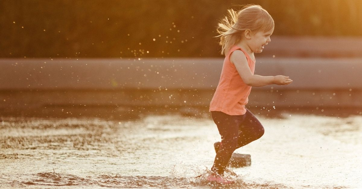 Cute little girl in a pink shirt running in a puddle