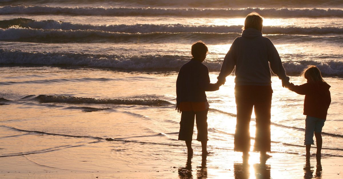 Mother and Two Children Enjoying the Sunset at the Beach