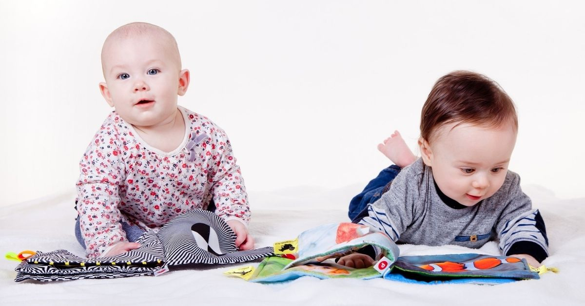Two cute babies playing with soft cloth books