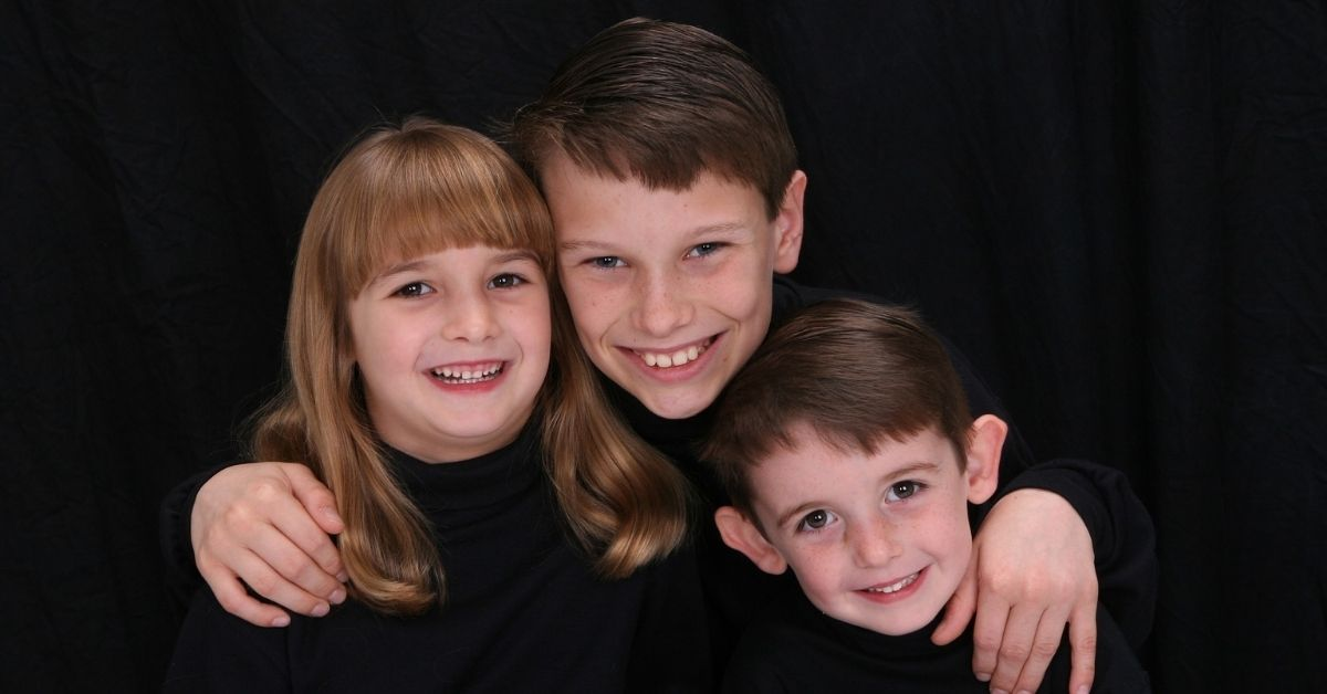 Three siblings in black clothing smiling at the camera