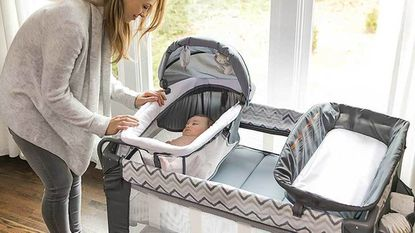 Mother rocking her baby in a Graco mini crib